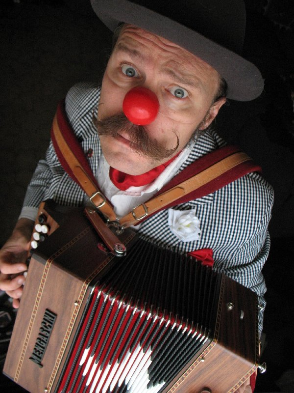 Guy Heathcote in his red nose playing the accordion