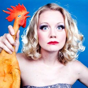 Juliet Jesket holding the neck of a Rubber Chicken with bright red lip stick.