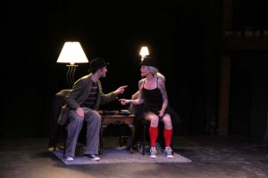 Josh Rice  &  CB Goodman sitting on stage with a light and lamp wearing bowler hats