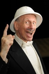 Richmond Shepard in a tux, holding up 1 finger, with a while hat.